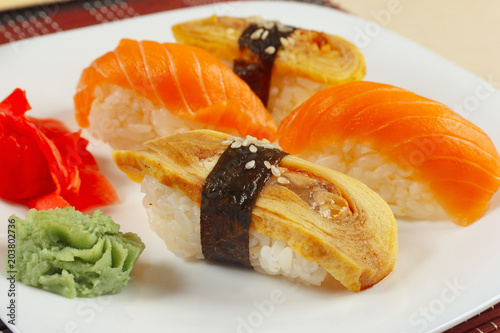 Fotobehang Sushi bar Sushi with omelet with eel and with salmon and ginger and wasabi on a black and red bamboo mat close up.