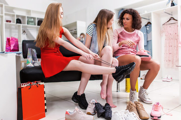 Best friends trying on different shoes talking sitting on a bench in a trendy fashion clothing store