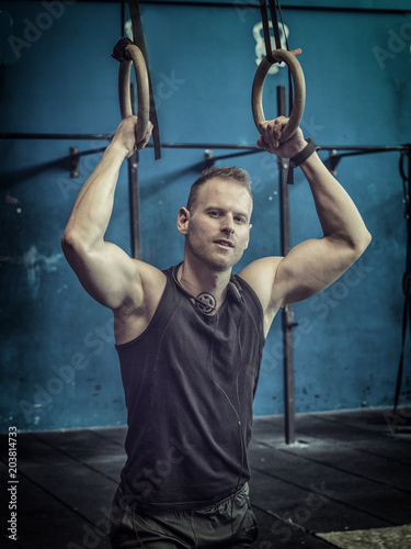 Handsome muscular young man athlete exercising in gym, hanging from rings.
