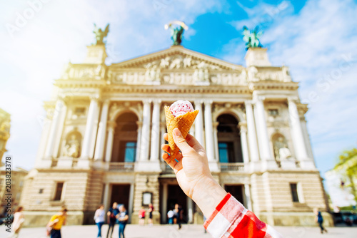 Foto Murales first-person view. woman hold ice cream in hand old european building on background