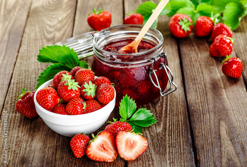 Fototapeta Homemade strawberry jam or marmalade in the glass jar and the basket of ripe strawberries on the wooden table