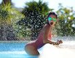 Woman relaxing in blue luxury swimming pool leisure on white natural stones vacation holidays
