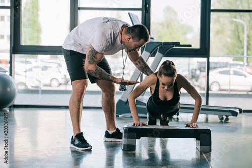 Fototapeta male personal trainer helping sportswoman to do push ups at gym