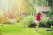 Kid girl playing with garden sprinkler in hot summer day. Water outdoor activities for children, happy childhood.