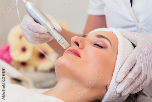 Close-up of the face of a woman relaxing in a modern beauty center during facial treatment with innovative technology for softening wrinkles and rejuvenation - 203885581