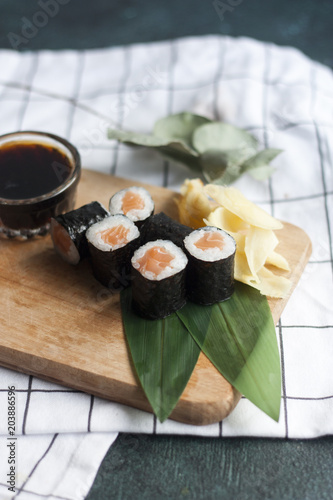 Plexiglas Sushi bar maki rolls with ginger and Soy sauce on wooden ditch