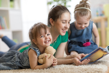 Young woman with children kids reading a book