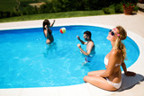 Friends playing ball games in pool - 203897122