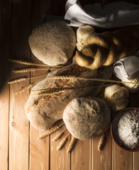 Traditional italian bread on the wooden table with pictorial light
