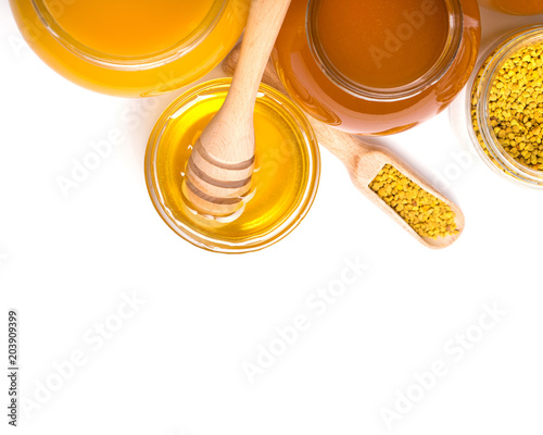 honey dipper and honey in jar on white background © Pakhnyushchyy