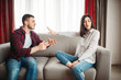 Wife sits on couch, angered husband yells on her