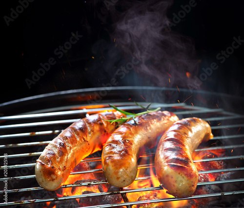 Grilled sausages on grill with smoke and flame - 203925168