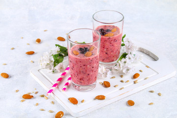 Blueberry smoothies of berries, banana and almonds in glasses with cocktail tubes on a white wooden board.