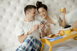 Young couple having a breakfast in the bed and looking at mobile phone