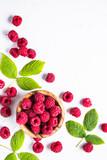 Fresh raspberries in wooden bowl on white table.