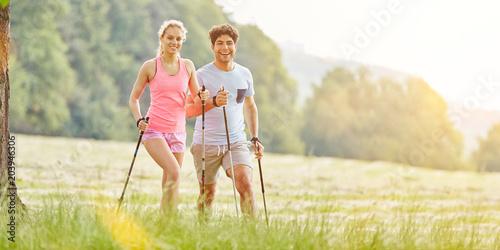 Fototapeta Paar beim Nordic Walking im Sommer