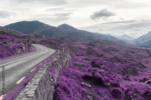 Fotobehang Aubergine fantasy, travel and nature concept - surreal view of asphalt road and rocky hills at connemara in ireland, infrared effect in purple color