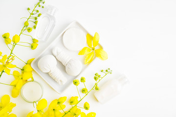 Bright spa background: candles and thai massage herbal bags with bottles and yellow flowers on white. Health, skin treatment concept © Evlira
