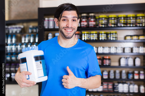 Happy sport man holding thumb up in store