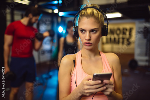 Wall mural Young blonde woman listens to her favorite music on headphones while she is in a gym