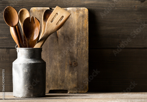 Wall mural Wooden kitchen cooking tools with spoons and spatula with menu board in front of rustic wooden board background