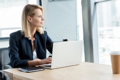 pensive buisnesswoman looking away while using laptop at workplace
