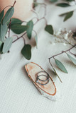 close up view of wedding rings on wooden decorative board and eucalyptus on tabletop