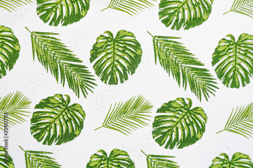 Palm leaves on white tablecloth fabric picnic texture. Textile, napkin, tablecloth. View from above, top. Traditional pattern and color, pattern background.