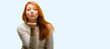 Beautiful young redhead woman expressing love, blows kiss at camera, flirting isolated over blue background