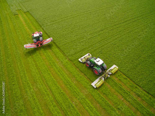 Aluminium Trekker Aerial view of two tractor mowing a green fresh grass field, farmer in a modern tractors mowing a green fresh grass field on a sunny day