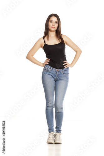 Foto Murales young woman in jeans and shirt stands on a white background