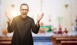 Priest religion man happy and surprised cheering expressing wow gesture at church