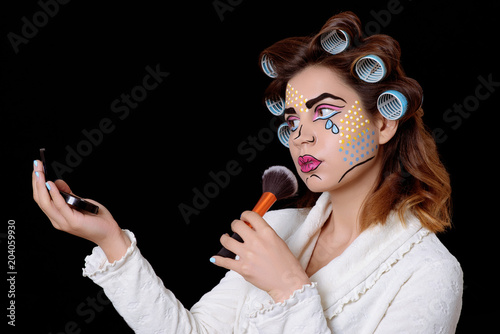 Model with comic pop art makeup looking to mirror, posing against black background.