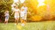Leinwandbild Motiv Familie und Kinder spielen Fußball im Garten