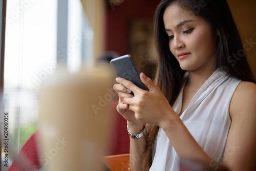 Fototapeta Young beautiful Asian businesswoman relaxing at the coffee shop