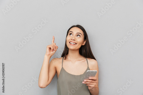Portrait of an excited asian woman holding mobile phone