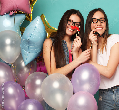 Two girls in stylish summer outfit , paper glasses and air balloons