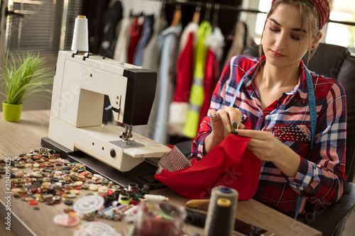 fashion designer woman sewing for new collection in her workshop