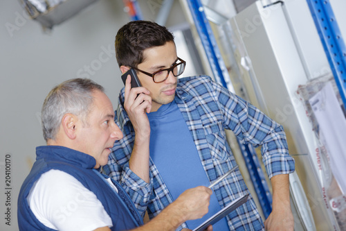 two workers talking and holding tablet pc and mobile phone