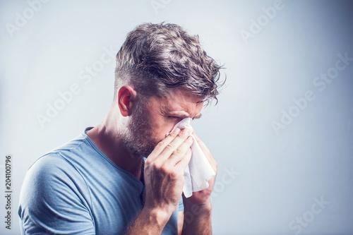 Leinwandbild Motiv Man sneezing in a tissue outdoors. Pollen allergy, Springtime.