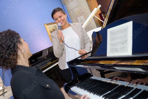 Fototapeta Woman singing being accompanied on the piano