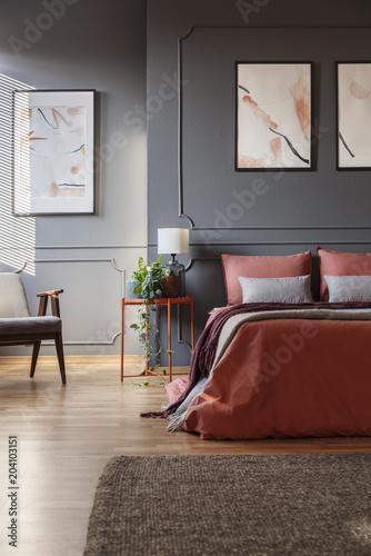 Pomarańczowy łóżko przed ciemną ścianą z formowania i białe plakaty obok metalowy stolik nocny z lampką na nim w sypialni wnętrza. Prawdziwe zdjęcie