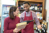salesman giving woman advice on buying bottle of red wine - 204105164