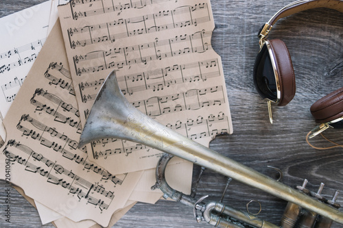 Headphones and trumpet near sheet music - 204106367