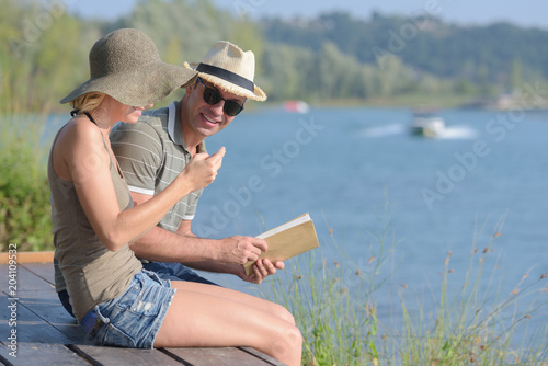 Couple sat on pier, holding book