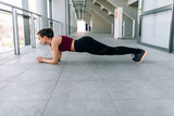 Young woman doing plank workout training indoors.