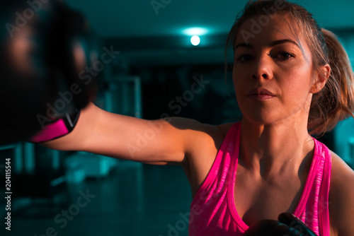Female boxer practicing her moves. Close-up. Looking at camera.