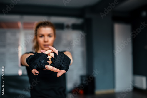 Blured image of girl preparing for a fight. Focus on foreground.