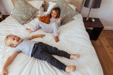 Joyful little children playing on bed - 204116541