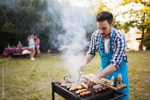 Wall mural Handsome male preparing barbecue
